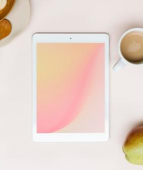 Maquete de tablet em um flatlay de mesa rosa
