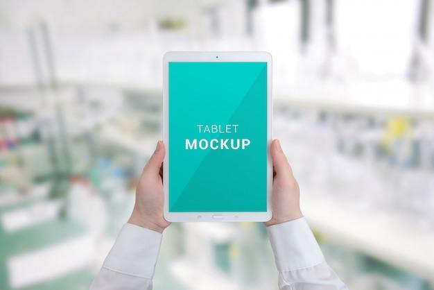 Maquete de tablet nas mãos de mulher. laboratório do hospital em segundo plano