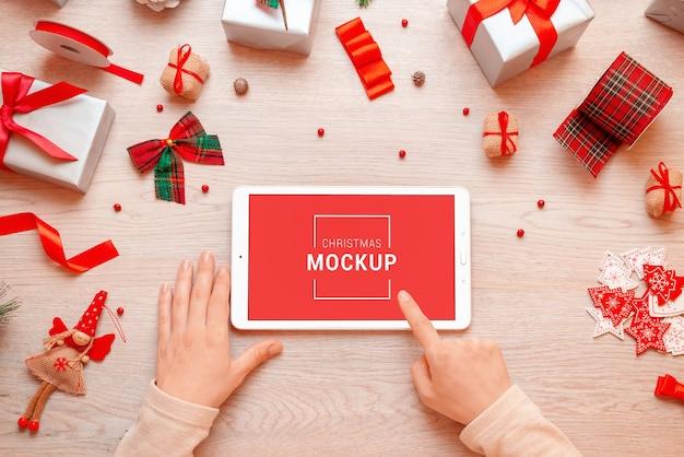Maquete de tablet rodeada de presentes e decorações de natal e ano novo