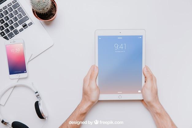Maquete de tecnologia com as mãos segurando o tablet