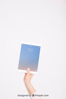 Maquete de tecnologia com mão mostrando o tablet