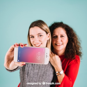 Maquete de tecnologia com mulheres apresentando smartphone