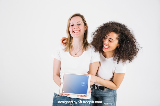 Maquete de tecnologia com mulheres felizes mostrando o tablet