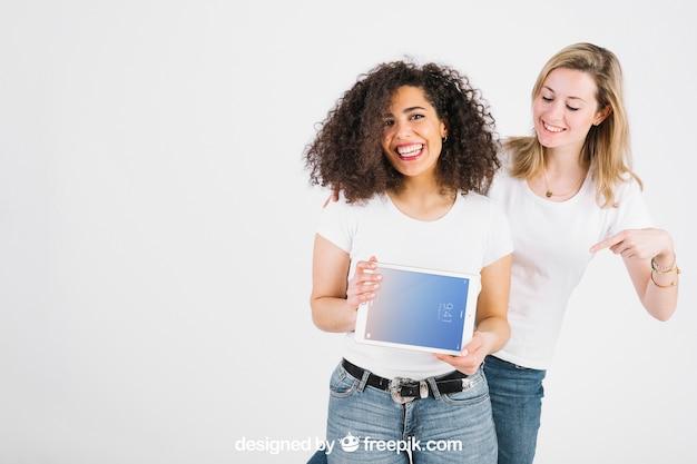 Maquete de tecnologia com mulheres mostrando tablet
