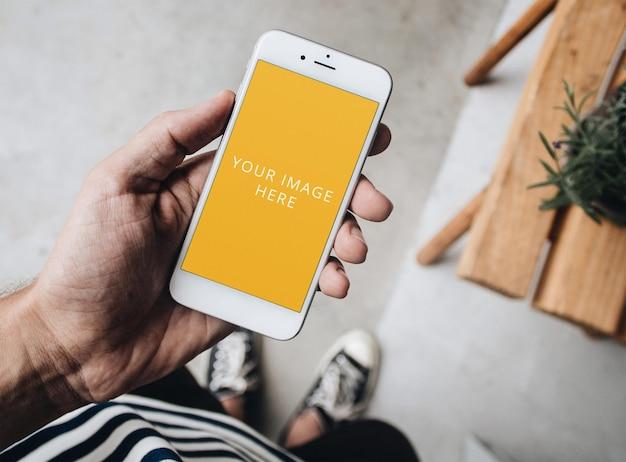 Maquete de tela de telefone branco segurado na mão na casa do loft