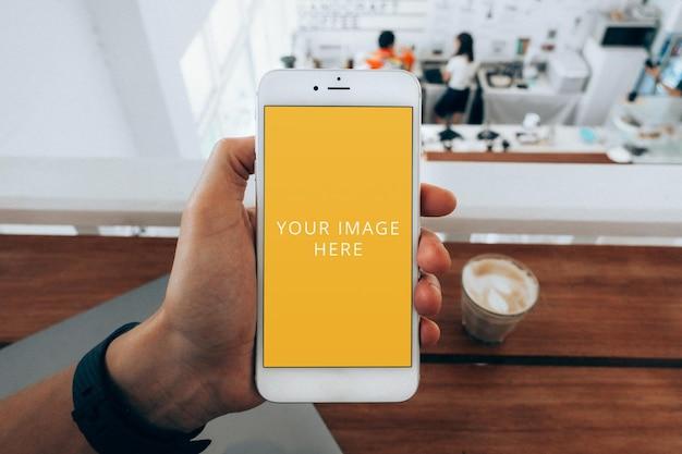 Maquete de tela de telefone branco segurado na mão no café