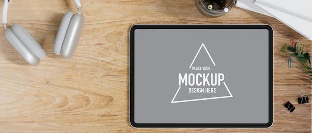 Maquete de tela em branco de tablet gráfico em mesa de escritório de madeira com fone de ouvido vista superior renderização em 3d