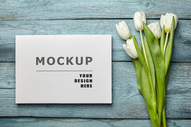Maquete de tela em branco e flores de tulipa branca na superfície plana de madeira azul clara