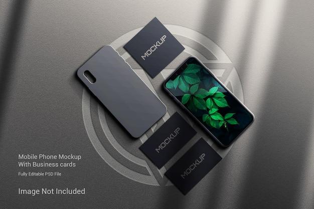 Maquete de telefone celular e ipad com cartões de visita e cabeçote posterior