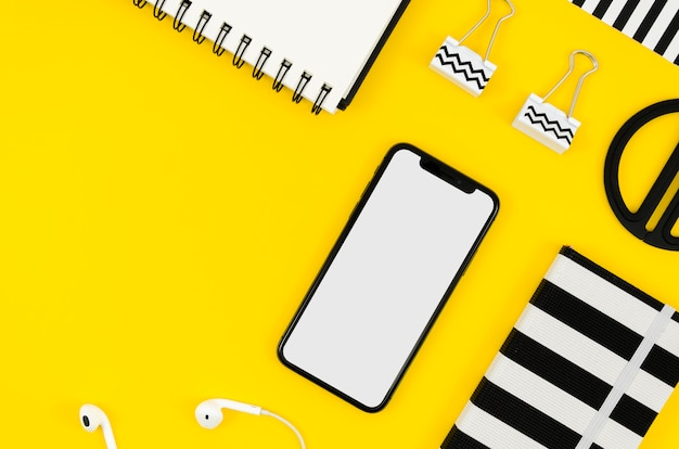 Maquete de telefone com vista superior com bloco de notas e fones de ouvido