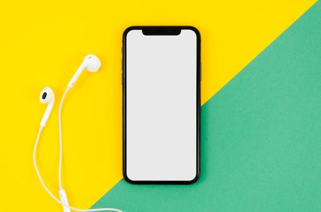 Maquete de telefone de vista superior com fones de ouvido