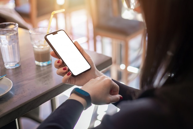Maquete de telefone inteligente. menina está olhando para uma pulseira inteligente. conceito de uso de aplicativos de saúde
