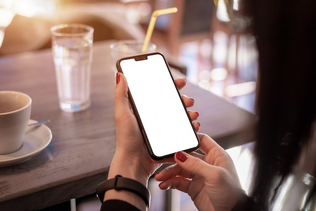 Maquete de telefone inteligente nas mãos da mulher. conceito de uso telefone app e pulseira inteligente