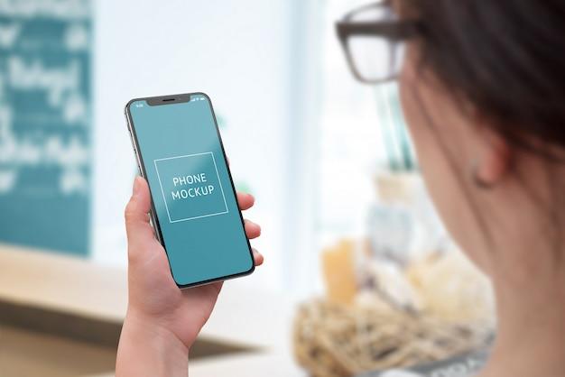 Maquete de telefone na mão da mulher. vista por cima do ombro. telefone inteligente moderno com bordas finas