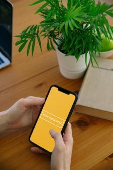 Maquete de telefone na mão no escritório