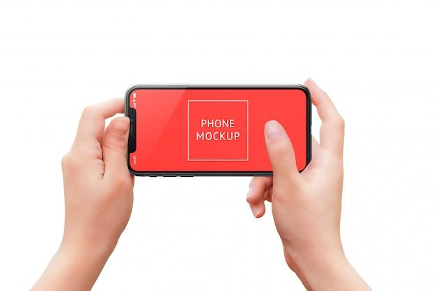 Maquete de telefone nas mãos da mulher. posição horizontal. conceito de uso de câmera ou aplicativo com o dedo na tela.