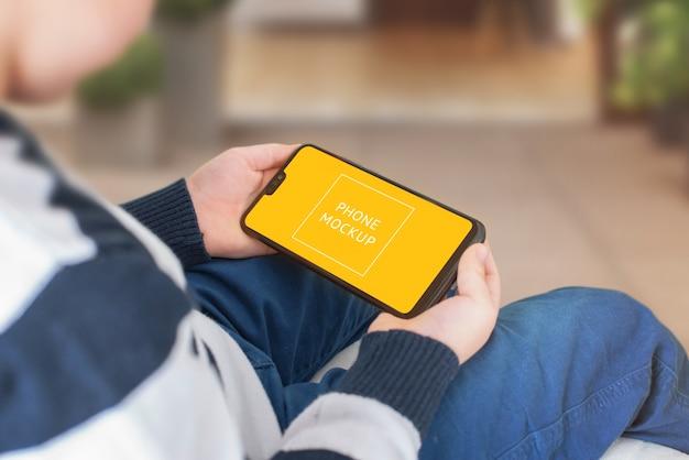 Maquete de telefone nas mãos do menino. posição horizontal.