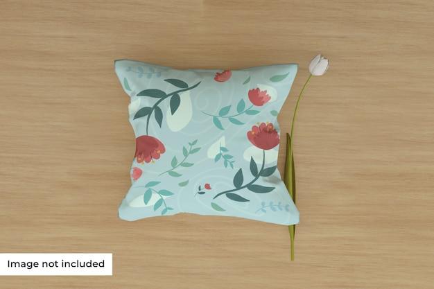 Maquete de travesseiro no chão com flor