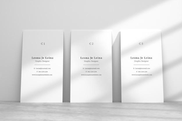 Maquete de três cartões de visita verticais com sobreposição de sombra