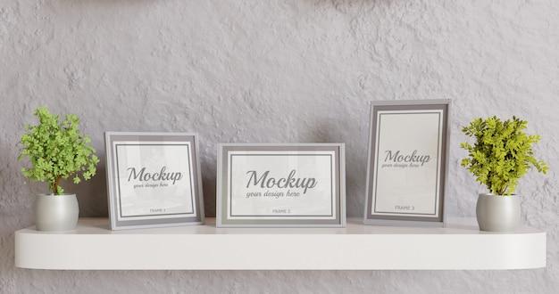 Maquete de três quadros na mesa da parede branca. maquete de moldura cinza