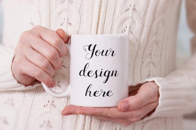 Maquete de uma caneca de café branco nas mãos da mulher