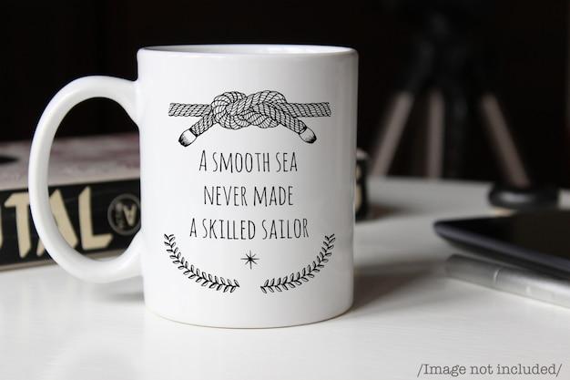 Maquete de uma caneca de café cerâmica branca em uma mesa