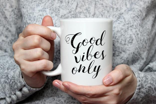 Maquete de uma caneca de café cerâmica branca na mão de uma mulher