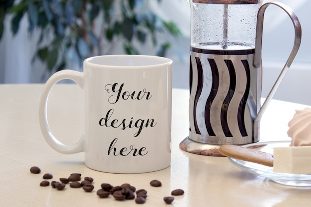 Maquete de uma caneca de café em uma mesa com doces e imprensa francesa