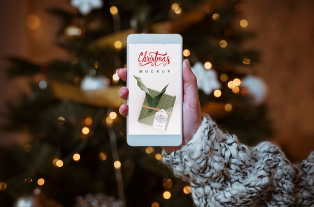 Maquete de venda de natal com a mão segurando o smartphone