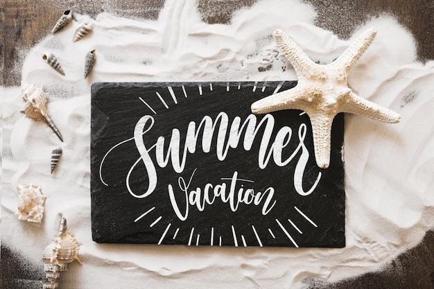 Maquete de verão com ardósia na areia
