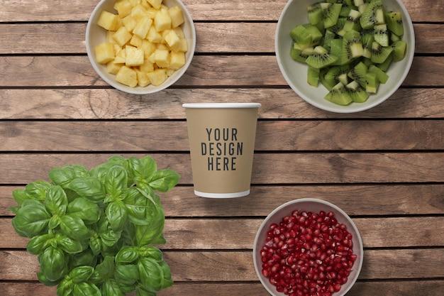 Maquete de xícara de café de papel e decoração de frutas