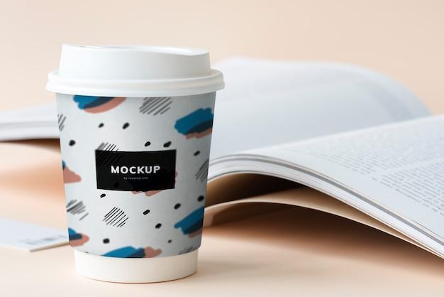 Maquete de xícara de café para viagem em uma mesa com um livro aberto