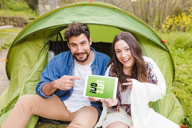 Maquete do acampamento de verão com o casal apontando para tablet