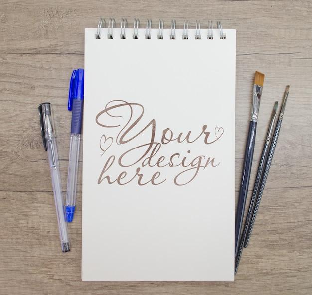 Maquete do bloco de notas com pincéis e caneta