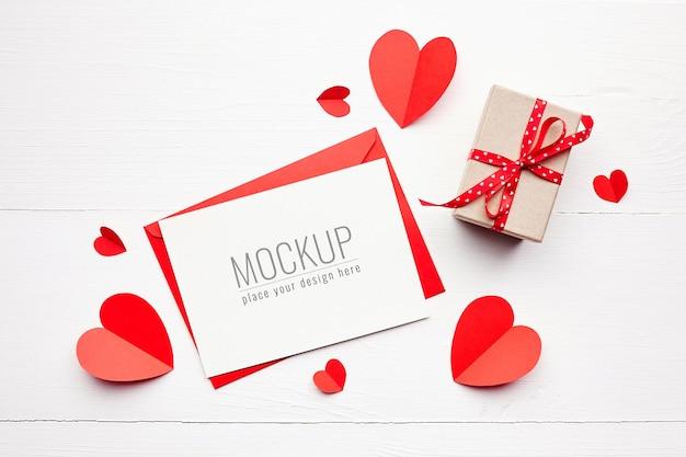 Maquete do cartão de dia dos namorados com caixa de presente e corações de papel vermelho