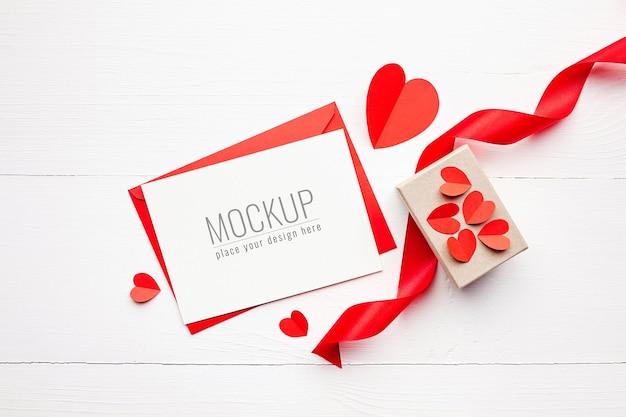 Maquete do cartão de dia dos namorados com caixa de presente, fita vermelha e corações de papel
