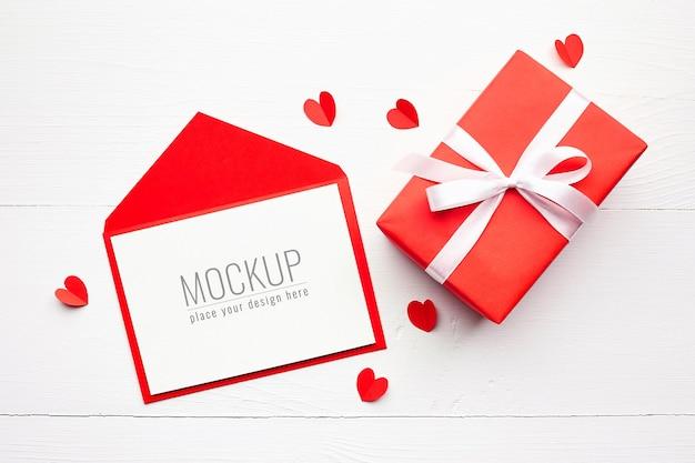 Maquete do cartão de dia dos namorados com caixa de presente vermelha e corações