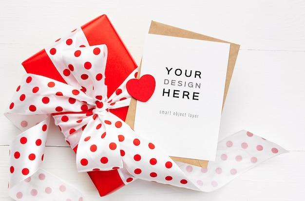 Maquete do cartão de dia dos namorados com coração vermelho e caixa de presente na mesa de madeira branca