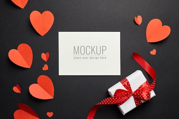 Maquete do cartão de dia dos namorados com corações de papel vermelho e caixa de presente