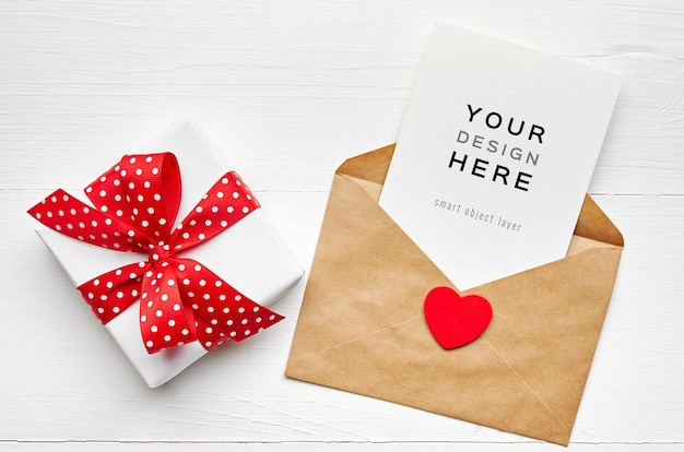 Maquete do cartão de dia dos namorados com envelope, coração e caixa de presente em branco