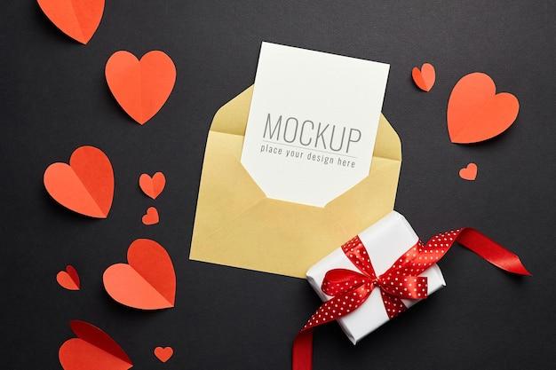 Maquete do cartão de dia dos namorados com envelope, corações vermelhos e papel de caixa de presente
