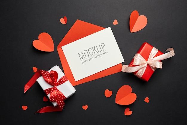 Maquete do cartão de dia dos namorados com envelope, corações vermelhos e papel de caixas de presente