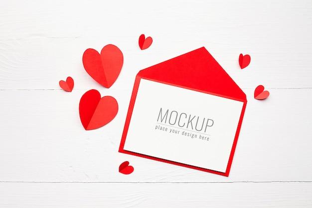 Maquete do cartão de dia dos namorados com envelope e corações de papel vermelho
