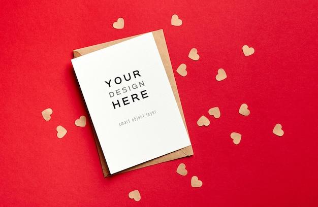 Maquete do cartão de dia dos namorados com envelope e pequenos corações de papel