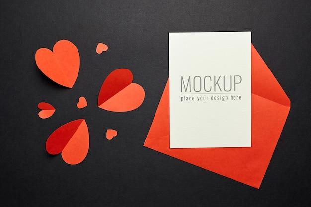 Maquete do cartão de dia dos namorados com envelope vermelho e corações na superfície de papel preto