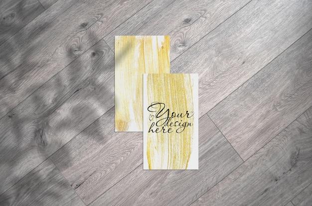 Maquete do cartão de visita em um fundo cinza de madeira com sombra de folhas