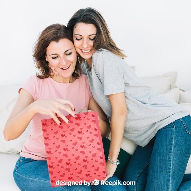 Maquete do dia das mães com a filha e a mãe olhando para o saco Psd grátis