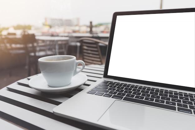 Maquete do laptop e café expresso quente na cafeteria