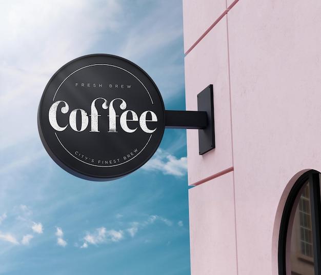 Maquete do logotipo com placa circular preta na fachada do prédio rosa