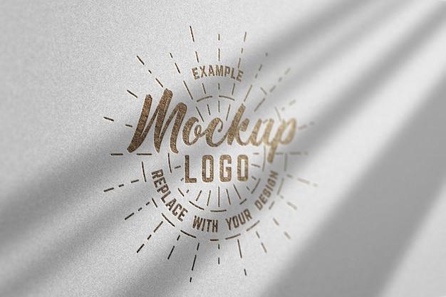 Maquete do logotipo com textura de ouro luxuoso em uma parede